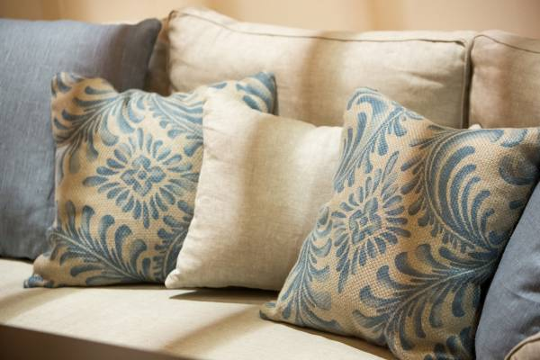 Blue and cream patterned cushions on a cream sofa