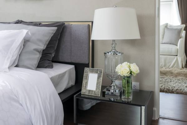 white grey and charcoal cushions on a modern bed with a glass side table